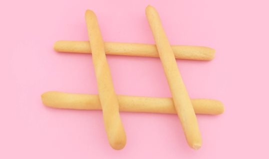 Hashtag made of fries on pink background