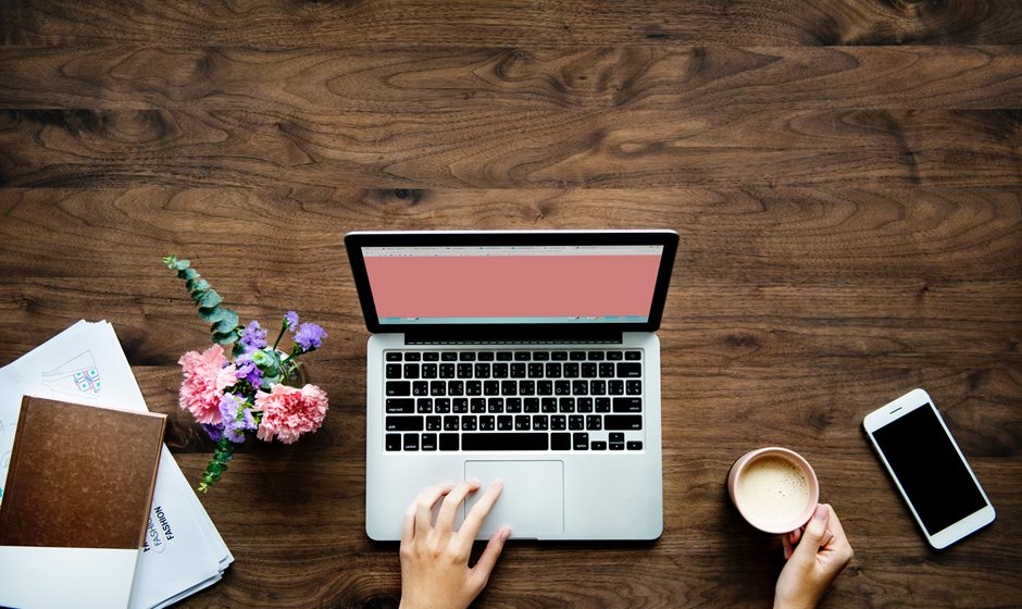 Blogger photo of a Macbook, coffee, iPhone and flowers